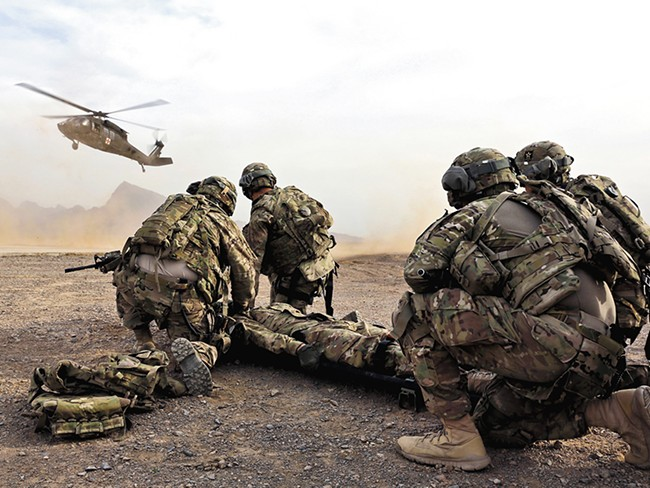 Soldiers in Afghanistan wait for a Black Hawk medevac helicopter to land before moving a simulated casualty during a training this month. - JOSH IVES