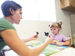 Speech Therapist Jen Wells leads a word exercise with 2-year-old student Abygail at Spokane Guilds\' School.