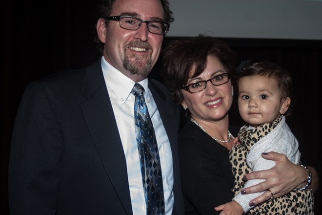 Spokane County District Court Judge 8 candidate Tim Trageser, left, poses for a photograph with his wife Tracy Trageser and thier granddaughter Aria. - ASHLEY TOMLINSON