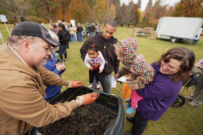 Spokane Master Composters volunteer Andy Smith, left, shows compost to (left to right) Charles McCall, holding his 2-year-old daughter Anaiah, and Ginger Blake, holding her 6-year-old daughter Gillian. - YOUNG KWAK