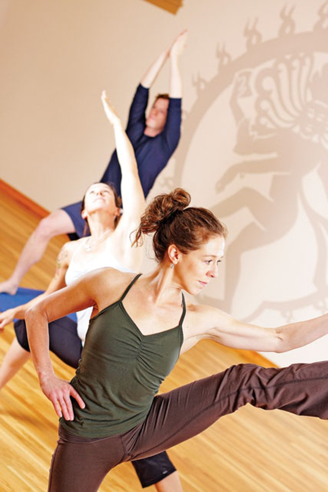 Spokane Yoga Shala owners Shelley Alkier (front) and Katie Gehn. Their student Luke Baumgarten (back) struggles into a rudimentary Ashtanga pose. [Young Kwak photo] - YOUNG KWAK