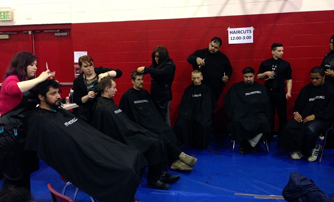 Students from the Paul Mitchell School in Spokane give haircuts to visitors. - CLARKE HUMPHREY
