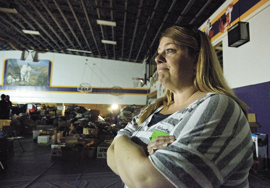 Suzette Ellis, a local relief volunteer, takes stock of the donations streaming into Pateros High School to help displaced residents recover from the fire. - JACOB JONES