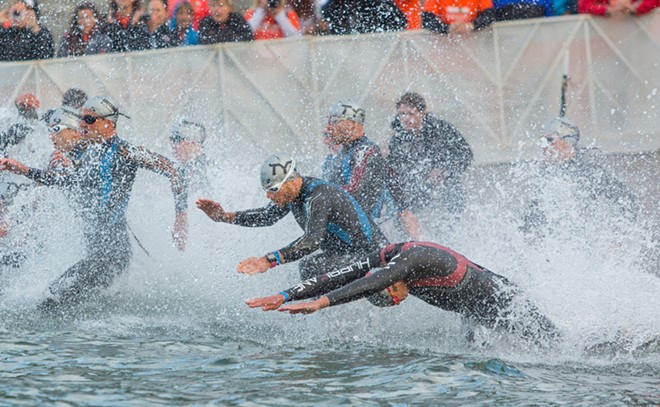 The professional men dive into Lake Coeur d'Alene at the start of the Ironman. - MATT WEIGAND