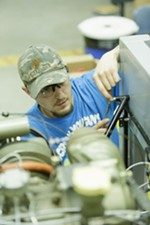 Third year student David Hoover loosens bolts before lifting a Continental 10360 engine.