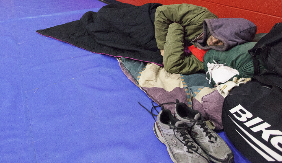 Tim Henry, of Nevada, lies down to sleep at a Spokane warming center in December. - YOUNG KWAK