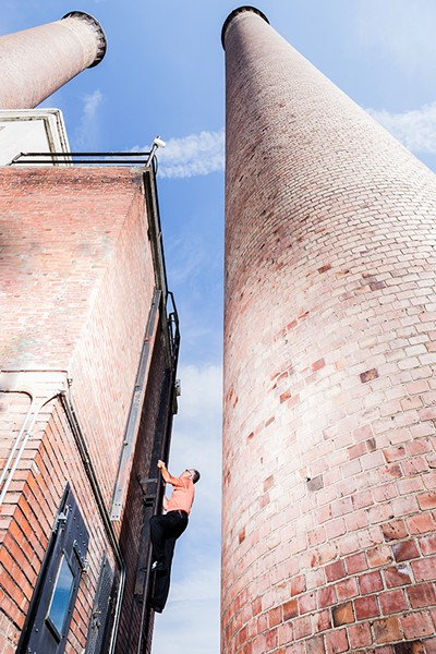 To access the top of the Steam Plant, you have to climb a ladder more than 90 years old. Here, Bill Bancroft, facilities operations manager, leads the way up. - STEPHEN SCHLANGE