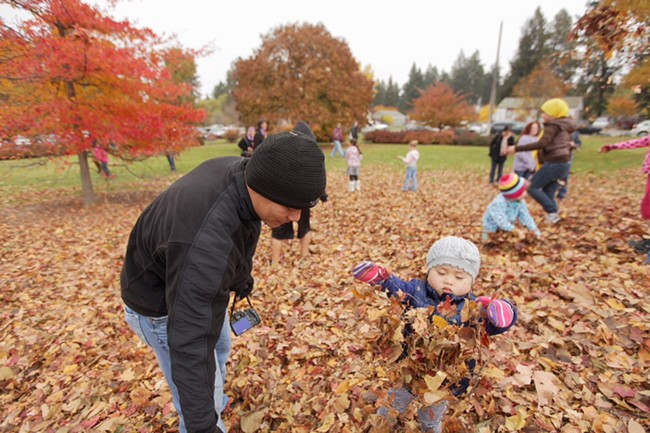 Tom Nguyen, left, and his 2-year-old daughter Hannah play in the leaves. - YOUNG KWAK