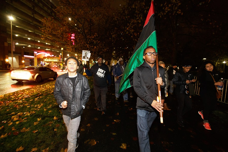 Twenty-year-old Isaiah Dolezal, right, carries a Pan-African flag as his 13-year-old brother Franklin Moore walks along his side down W. Spokane Falls Blvd. - YOUNG KWAK