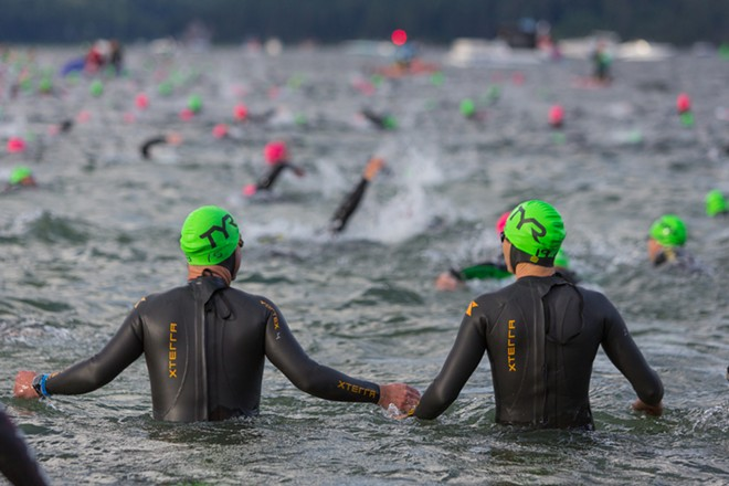 Two friends and competitors enter the brisk water of Coeur d'Alene Lake for the start of the Ironman. - MATT WEIGAND