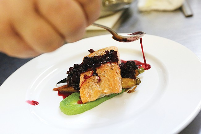 Chef Jennifer Parkinson carefully plates salmon with huckleberry chutney. - YOUNG KWAK