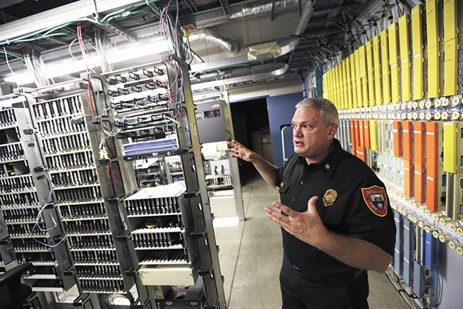 Spokane Fire Chief Brian Schaeffer showcases the innards of the Combined Communications Center — which currently holds multiple dispatch agencies. - YOUNG KWAK