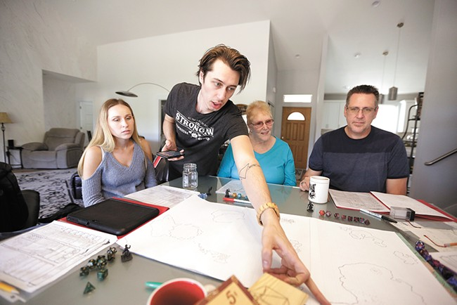 Dungeon master Josh Adrian, second from left, points out a spot on the game map to his sister Kayla (far left), grandmother Reggie Adrian and dad Joel Adrian. - YOUNG KWAK