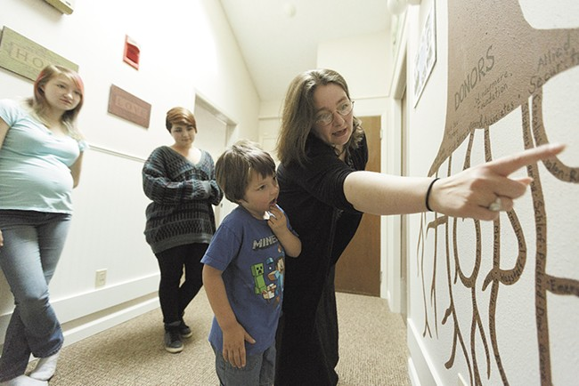 Angela Friedrich shows her 5-year-old son, Bert, a mural representing the donors who contributed to Family Promise of Spokane, which has helped the Friedrich family. - YOUNG KWAK