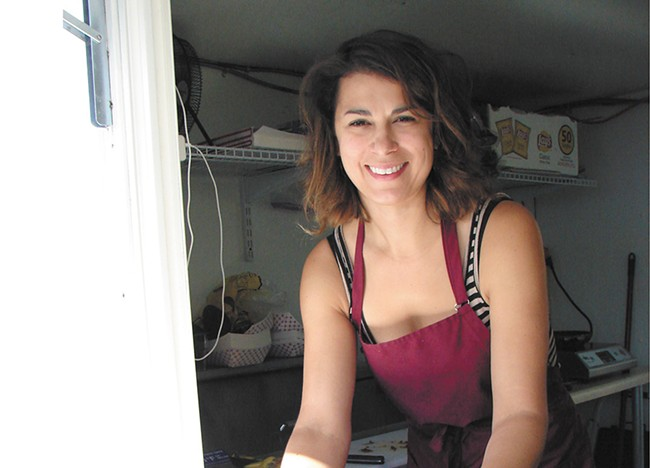 Amie Wolf in her Baconapolis food cart in Sandpoint. - CARRIE SCOZZARO