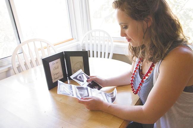 As she looks at sonograms, McNamara reflects on the process of getting pregnant. - JENNIFER DEBARROS PHOTO