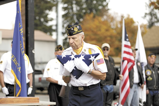 Sgt. Harold Markiewicz, a member of American Legion Post 143 in Post Falls, delivers a flag to Parkinson's family in his honor. - YOUNG KWAK
