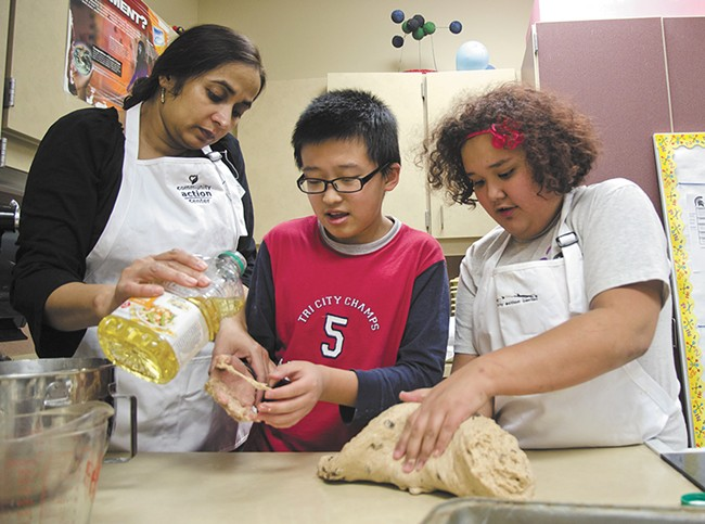 Tony and Napua learn breadmaking from volunteer Abtesam Khan at Pullman's Lincoln Middle School. - JACOB JONES