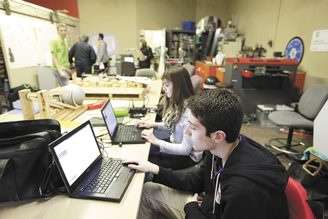 Students Joe Broader, right, and Crista Falk work on programming for the team's robot. - YOUNG KWAK