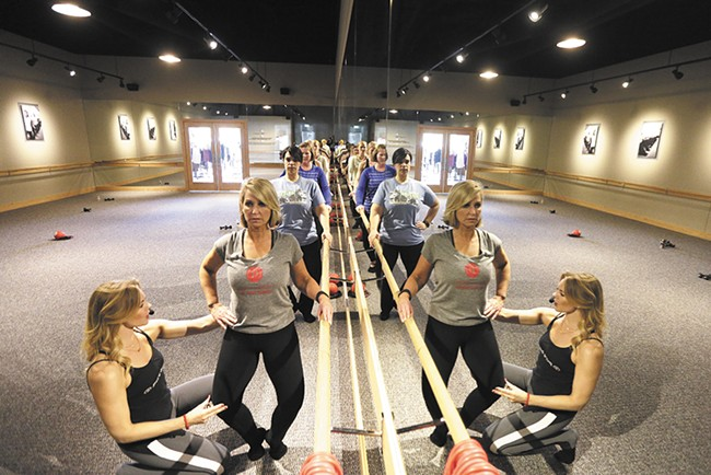 Pure Barre owner Katie Wood helps Leslie Lowe fine-tune a pose. - YOUNG KWAK
