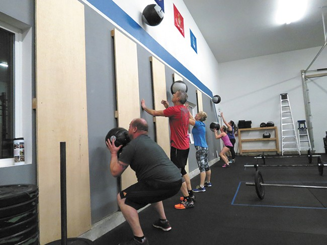 Strength training in small groups fosters bonding at CrossFit.