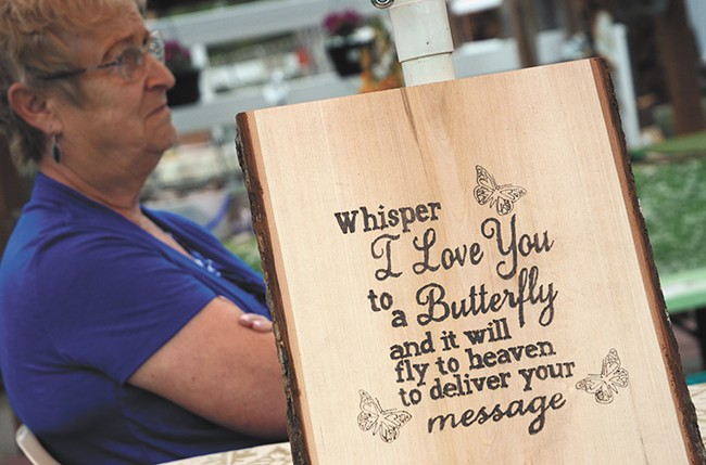 Karen Webber with a sign that was made for the family following Scotty's death, highlighting the significance of butterflies in their house. - MIKE SALSBURY