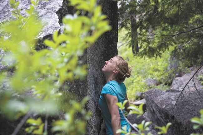 Carolyn Coffey makes her way up a boulder. - TARYN PHANEUF
