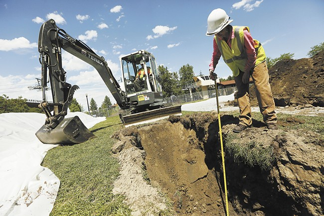 Fort Walla Walla Museum archaeologist Ashley Morton inspects a trench in Riverfront Park's Gondola Meadow, which was once a prominent area for the Spokane Tribe before becoming an early part of downtown Spokane. - YOUNG KWAK