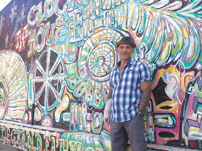 Muralist Nate O'Neill, with his work at the Clock House, sees North Hill as an arts haven. - DAN NAILEN