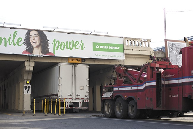 A truck, like several others this year, gets wedged underneath the railway bridge downtown, despite the sign warning of the low height. - YOUNG KWAK