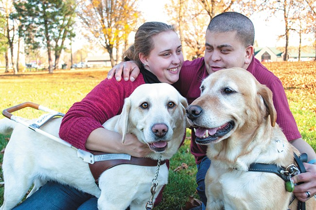 Katrina and Ryan Strickland with their service dogs, Madison and Huntley, at Franklin Park in Spokane. - SARAH PHILP