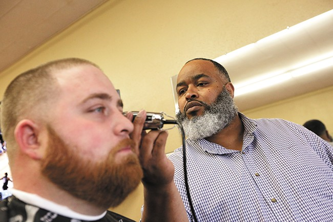 Jay Troutt, right, draws customers from across the region to his barbershop. - YOUNG KWAK