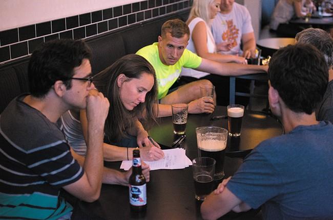 Teams discuss answers at Press's trivia night. - STUART DANFORD