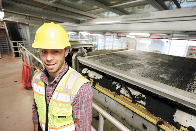 Kyle Arrington, a chemist with Spokane Wastewater Management, shows the press that removes excess water from biosolids. - YOUNG KWAK