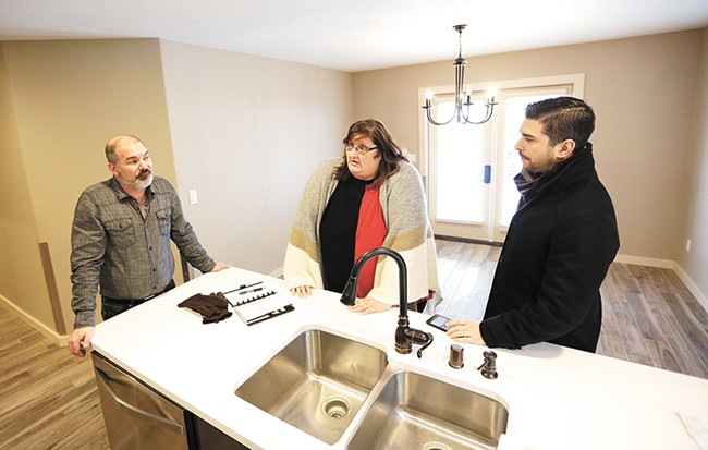 """Project Managers Colt Utley and Jacob Pollowitz (left, right) stand with service provider Rachell Redman in the kitchen of a newly remodeled """"health home."""" - YOUNG KWAK"""