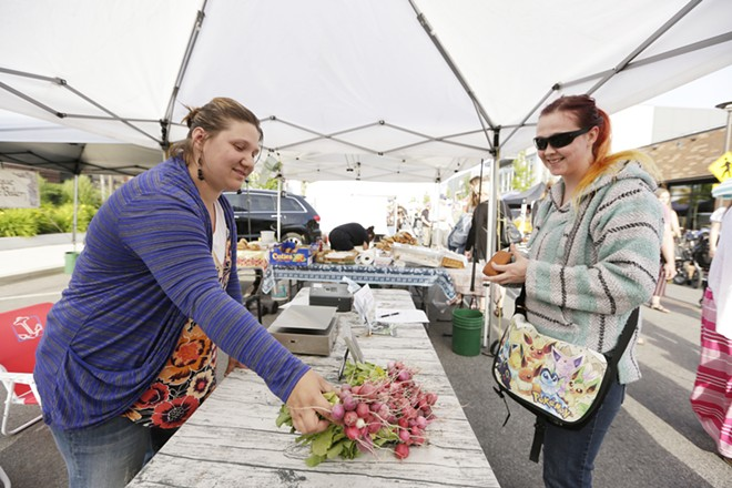 Red Beard co-owner Jessica Kaluza sells radishes to a customer in Kendall Yards. - YOUNG KWAK