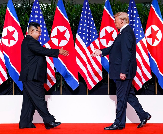 President Donald Trump and Kim Jong Un of North Korea greet each other before their meeting on Sentosa Island in Singapore, June 12, 2018. - DOUG MILLS/THE NEW YORK TIMES