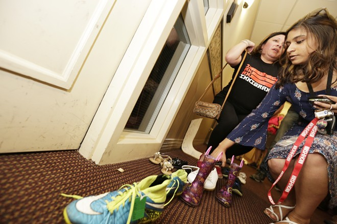 Sarah Dixit places shoes outside the office of Rep Cathy McMorris Rodgers as Lili Navarrete looks on, during an immigrant rights protest in Spokane, Thursday, July 5. - YOUNG KWAK