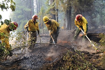 "A group of firefighters work to knock out a hotspot in a wilderness area near Bucktail,  Calif., Aug. 1, 2018. Officials said the Carr Fire was one of 17 major fires across California that have consumed more than 450,000 acres. Gov. Jerry Brown called it the ""new normal."" - JIM WILSON/THE NEW YORK TIMES"
