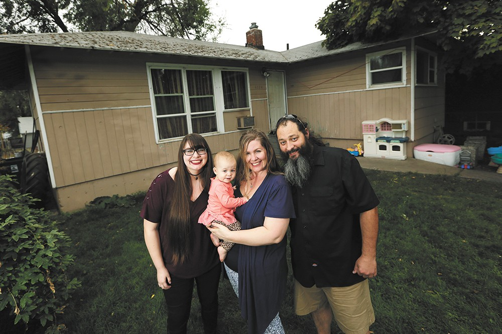 FROM RIGHT: William and Autumn Nixdorf, with daughters Avalynn (1) and Haley (17) in front of the home they saved from foreclosure. - YOUNG KWAK