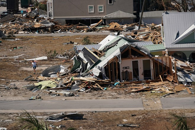 A woman cleans debris around a home in the aftermath of Hurricane Michael, in Mexico Beach, Fla., Oct. 13, 2018. By the end of this century, some parts of the world could face as many as six climate-related crises at the same time, researchers have concluded. - CHANG W. LEE/THE NEW YORK TIMES