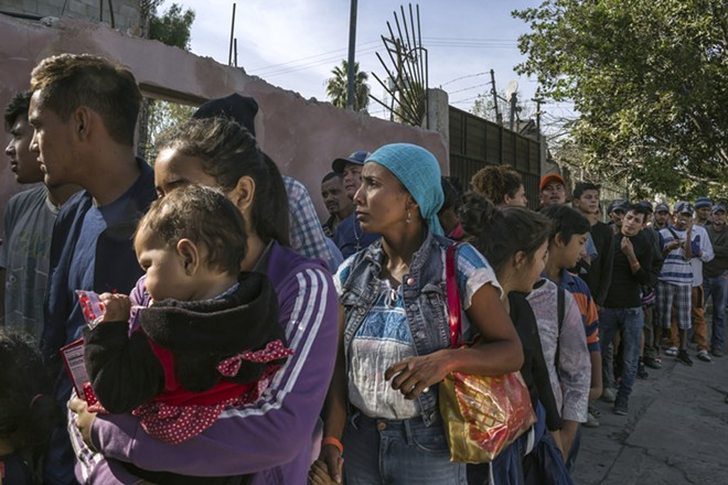 Melissa Guzmán, center, from Copán in Honduras, waits in line for food with other migrants outside a recently arranged shelter in Tijuana, Mexico, Nov. 17, 2018. A federal judge on Nov. 20 ordered the Trump administration to resume accepting asylum claims from migrants no matter where or how they entered the U.S., dealing at least a temporary setback to the president's attempt to clamp down on a huge wave of Central Americans crossing the border. - MAURICIO LIMA/THE NEW YORK TIMES