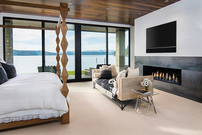 A dramatic fireplace complements expansive water views in this Coeur d'Alene master suite. - JOEL RINER PHOTO