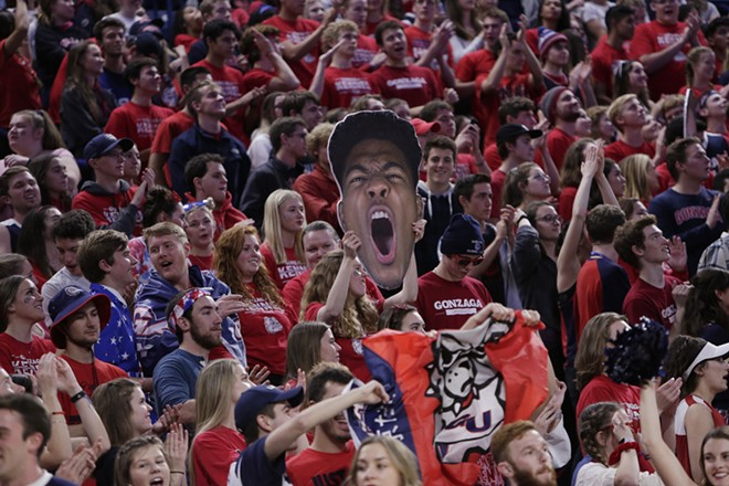 A fan holds a cutout photograph of Gonzaga forward Rui Hachimura. - YOUNG KWAK