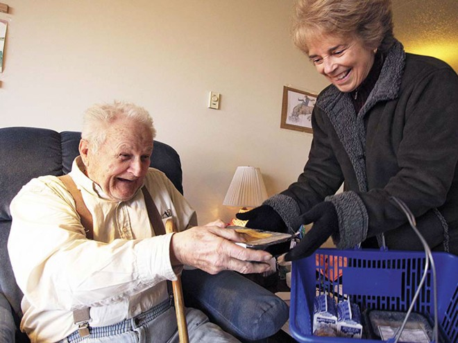 Judy Reilly, right, hands a Meals on Wheels delivery to 87-year-old Emanual Kennedy. - YOUNG KWAK