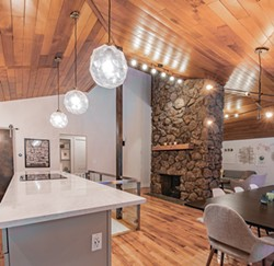 The carpeted conversation pit in front of the fireplace had a groovy vibe, but ultimately the homeowners removed it to improve flow in the open living area. - ERICK DOXEY PHOTO