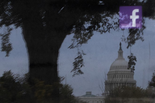 A Facebook logo, seen in reflection on an advertising board near the U.S. Capitol in Washington, Oct. 25, 2018. Facebook could face more intense government scrutiny, as regulators have decided that the Federal Trade Commission will oversee antitrust complaints about the company, according to two people with knowledge of the matter in 2019. - TOM BRENNER/THE NEW YORK TIMES