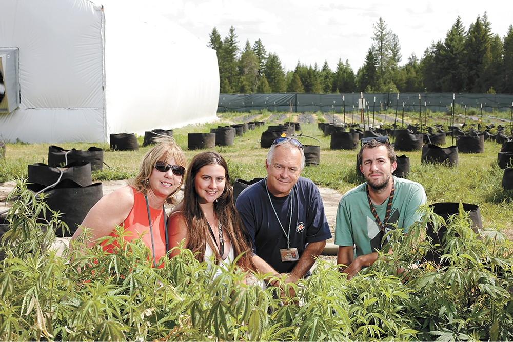 The team behind Orange State Cannabis poses in the outdoor cannabis field. - YOUNG KWAK PHOTO