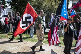 A white nationalist carries a Nazi flag during a protest in Charlottesville, Va., Aug. 12, 2017. - EDU BAYER/THE NEW YORK TIMES