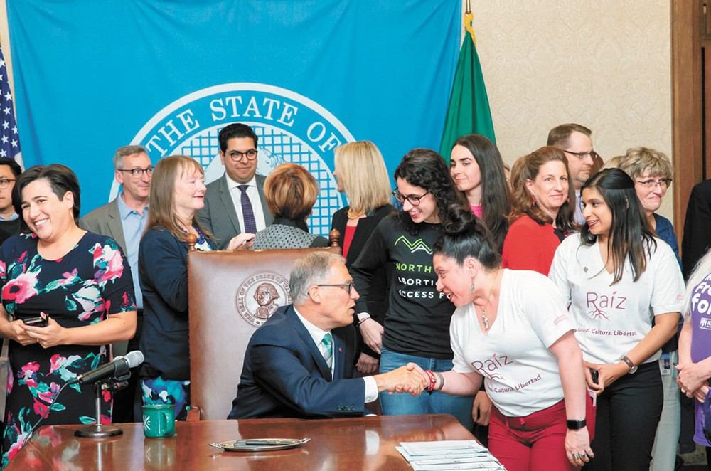 Lili Navarrete shakes Gov. Jay Inslee's hand at the Reproductive Health Access for All Act bill signing.